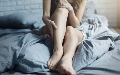 Eine Frau sitzt auf einem Bett und reibt ihren rechten Unterschenkel.