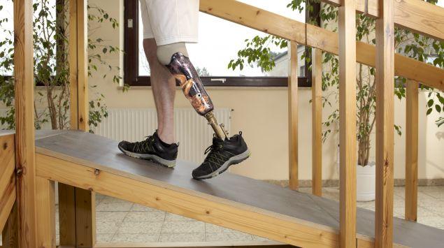 Ein Mann mit Beinprothese läuft eine Schräge rauf.