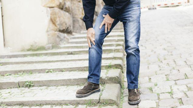 Ein Mann greift sich ans schmerzende Bein.