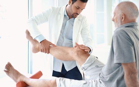 Beinschmerzen: Ein Arzt untersucht das Bein eines Mannes.