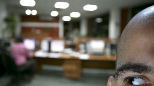 Ein Mann in einem Büro beobachtet die Szenerie im Hintergrund.