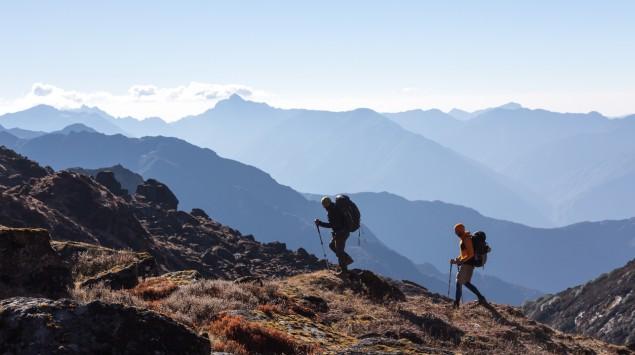 Zwei Personen wandern einen Berg hinauf.