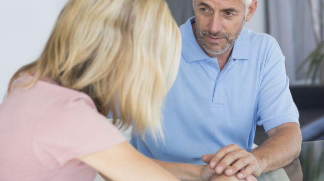 Ein Mann legt seine Hand beruhigend auf die Hände einer Frau.