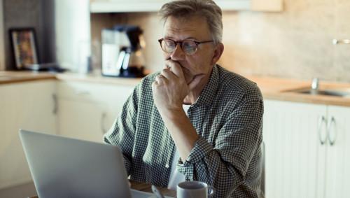 Ein Mann sitzt am Frühstückstisch und schaut besorgt auf seinen Laptop.