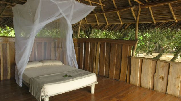 Zu sehen ist ein mit einem Moskitonetz ausgestattetes Bett in einem Öko-Resort im tropischen Regenwald.