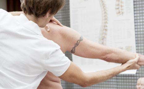 Arthrose: Ein Arzt testet, wie weit der Arm eines Mannes bewegbar ist.