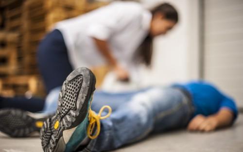 Eine Frau kümmert sich um einen bewusstlosen, am Boden liegenden Mann.