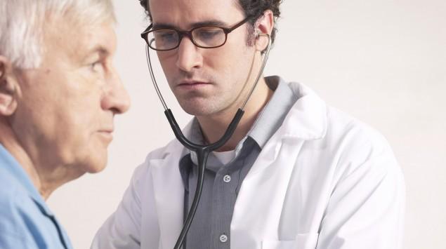 Ein junger Arzt hört einen älteren Mann mit dem Stethoskop an der Brust ab.