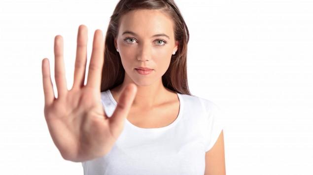 Eine Frau streckt abwehrend eine Hand aus.