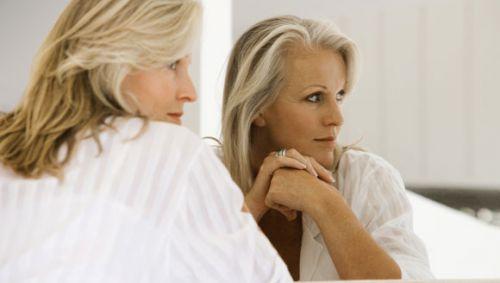 Das Bild zeigt eine ältere Frau, die vor einem großen Spiegel sitzt.