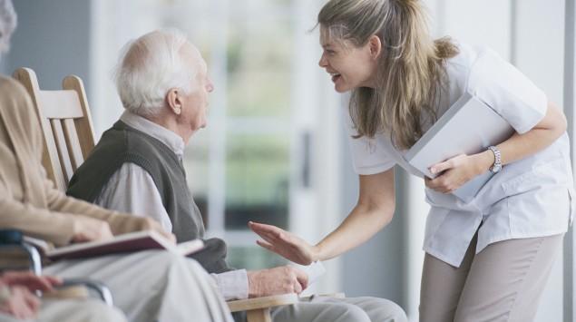 Eine Altenpflegerin spricht mit mit einem älteren Mann.