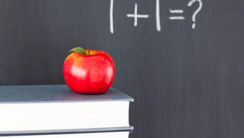 Eine Tafel mit einer Rechenaufgabe, im Vordergrund Bücher, auf denen sich ein Apfel befindet.