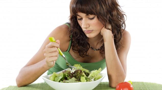 Das Bild zeigt eine Frau, die im Essen stochert.