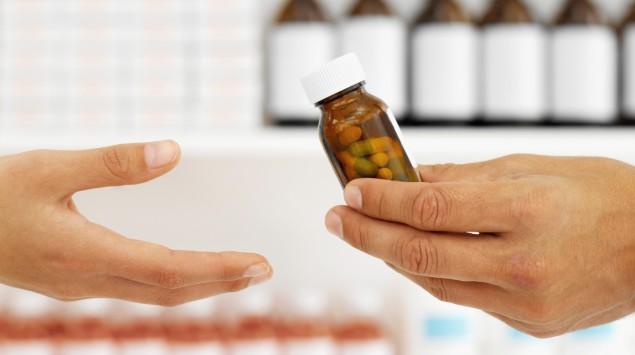 Jemand überreicht einer Person ein Arzneimittel.