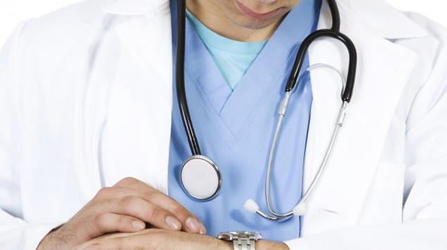 Ein Arzt schaut auf seine Armbanduhr.