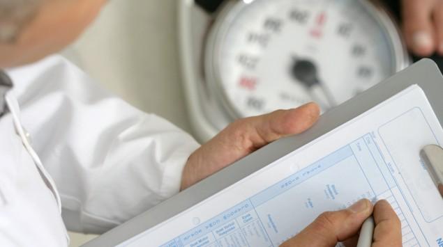Ein Arzt wiegt einen Patienten und notiert das Gewicht.