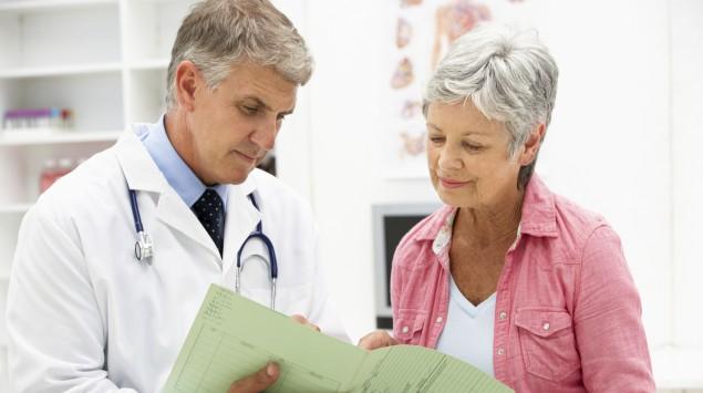 Ein Arzt erklärt einer älteren Patienten etwas.
