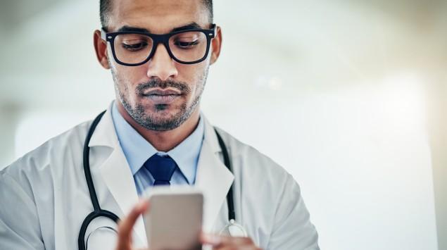 Eine Arzt gibt eine Nummer im Smartphone ein.