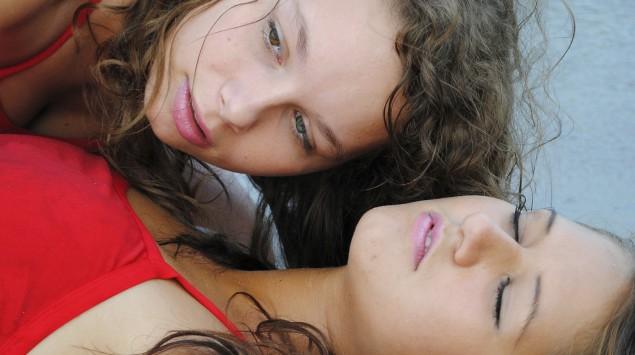 Eine Frau überprüft die Atmung einer Bewusstlosen.