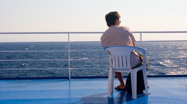 Das Bild zeigt einen Mann, der auf dem Deck eines Schiffes sitzt.