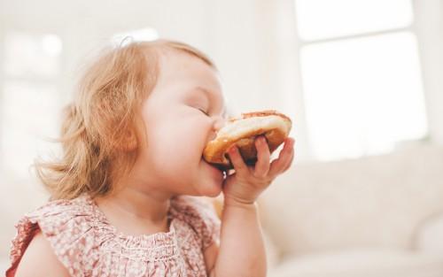 Ein Baby isst ein Stück Brötchen.