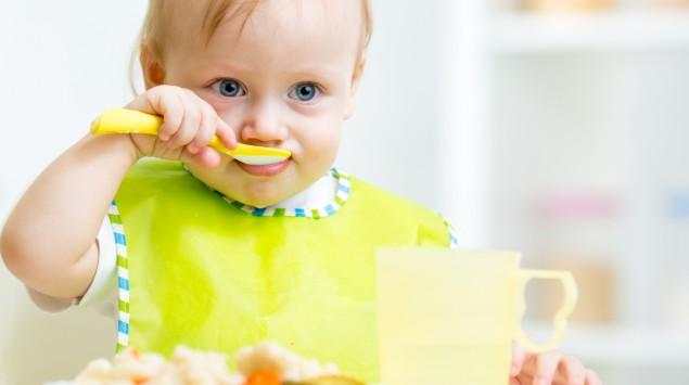 Ein Baby hält isst alleine seinen Brei