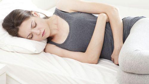 Eine Frau liegt mit Bauchschmerzen auf dem Bett.