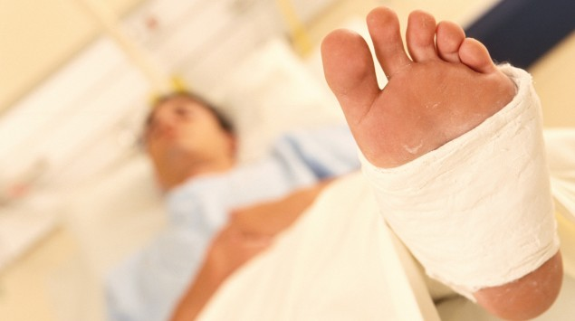 Eine man liegt im Krankenhaus und hat ein Bein in Gips.