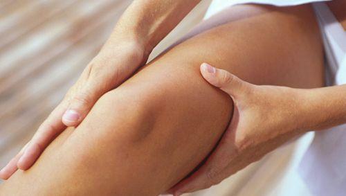 Eine Frau massiert ihr Bein.