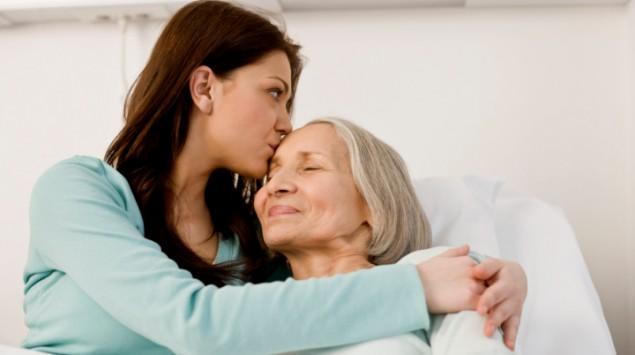 Eine junge Frau leistet einer älteren, im Bett liegenden Frau, Beistand.