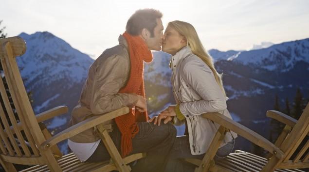 Ein Pärchen küsst sich, im Hintergrund sieht man Berge.