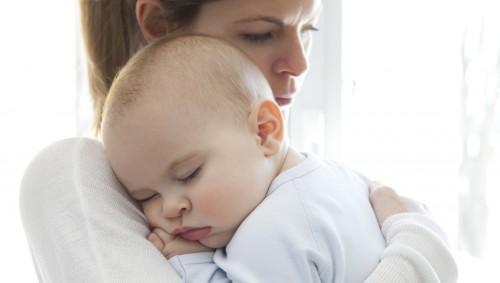 Eine Mutter hat ihren kleinen Sohn auf dem Schoß und schaut ihm über die Schulter.