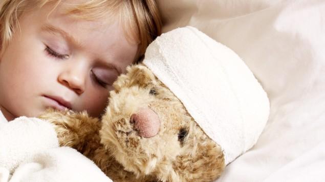 Das Bild zeigt ein schlafendes Kind mit einem Teddy im Bett.