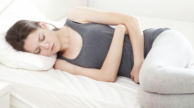 Man sieht eine liegende Frau, die die Arme schützend vor dem Bauch verschränkt.