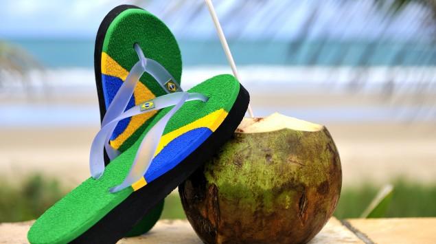 Man sieht Flipflops mit der brasilianische Flagge als Aufdruck und eine angeschnittene Kokosnuss mit Strohhalm.