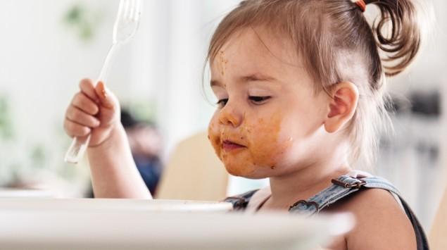Ein Mädchen sitzt verschmiert vor seinem Essen.