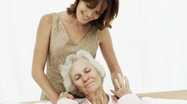 Eine junge Frau steht hinter einer älteren Frau, die im Bett liegt.