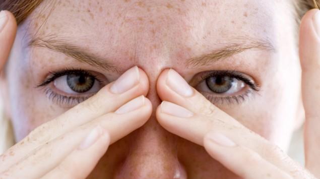 Eine Frau fasst sich an die Augen.
