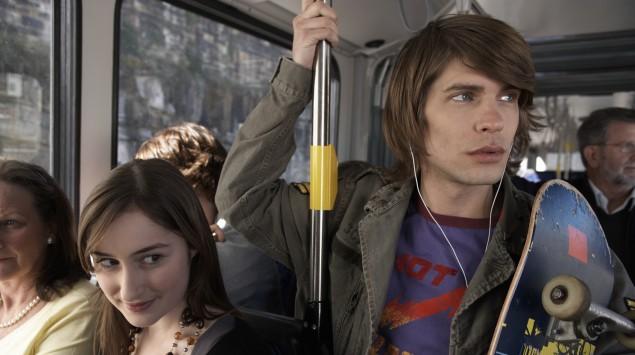 Ein Junge mit einem Skateboard fährt im Bus und hält sich fest.