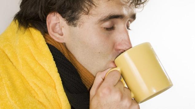 Ein Mann mit einer Decke trinkt eine Tasse Tee.