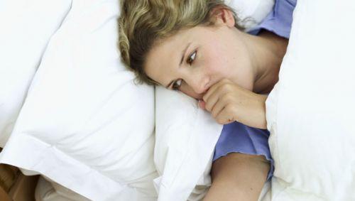 Ein Frau liegt im Bett und hustet.