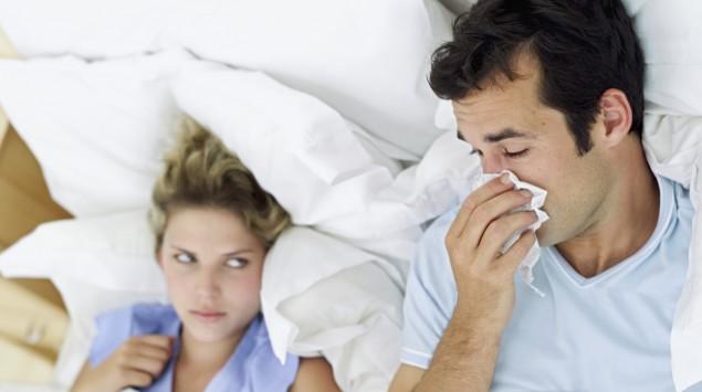 Eine Frau und ein niesender Mann liegen im Bett.