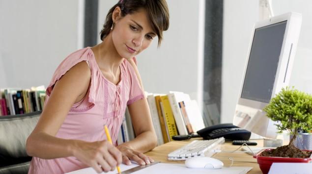 Eine Frau sitzt im Büro am Schreibtisch.