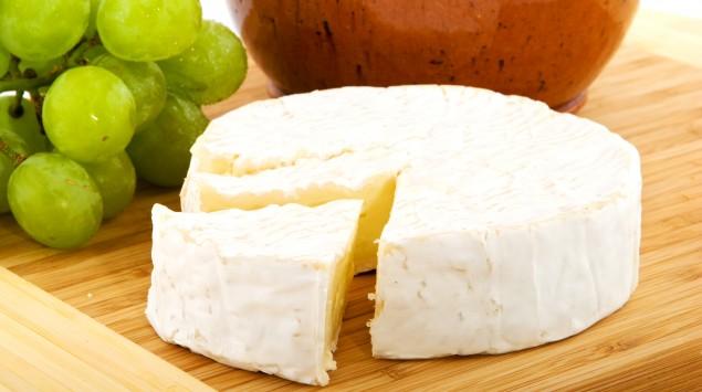 Man sieht ein Stück Camenbert-Käse und Weintrauben.