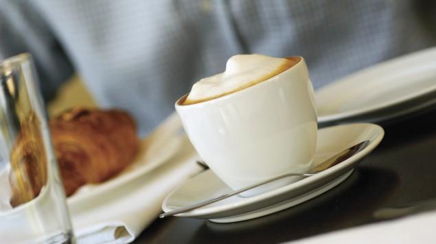 Das Bild zeigt eine junge Frau, die eine Tasse mit Cappuccino in der Hand hält.