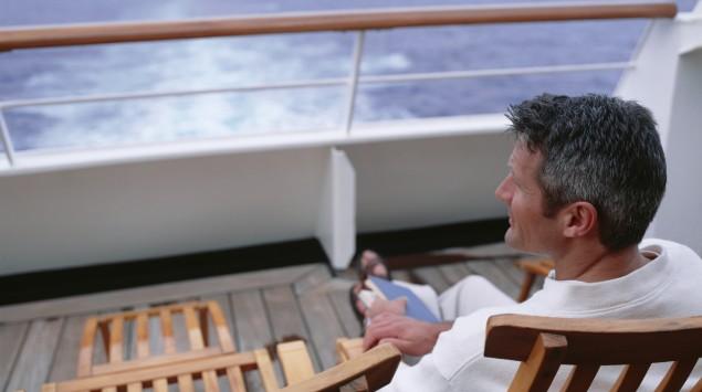Das Bild zeigt einen Mann, der an Deck eines Schiffes sitzt.