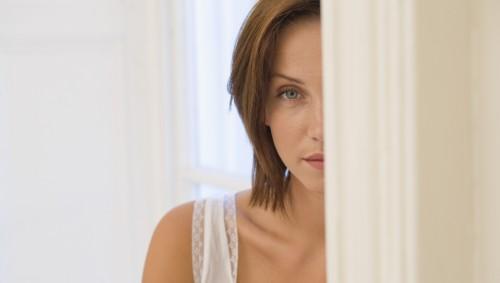 Eine Frau schaut halb hinter einem Vorhang hervor. Sie sieht bedrückt aus.