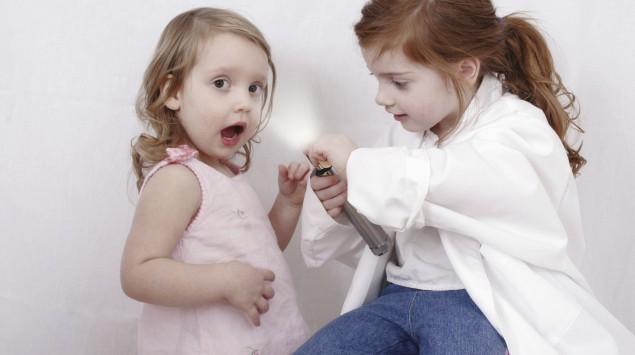 Zwei kleine Mädchen spielen Arztbesuch.