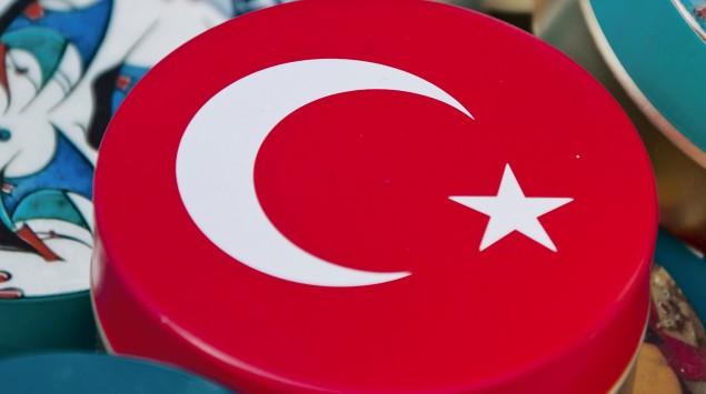Man sieht mehrere kleine Blechdosen, eine ist mit der türkischen Flagge verziert.
