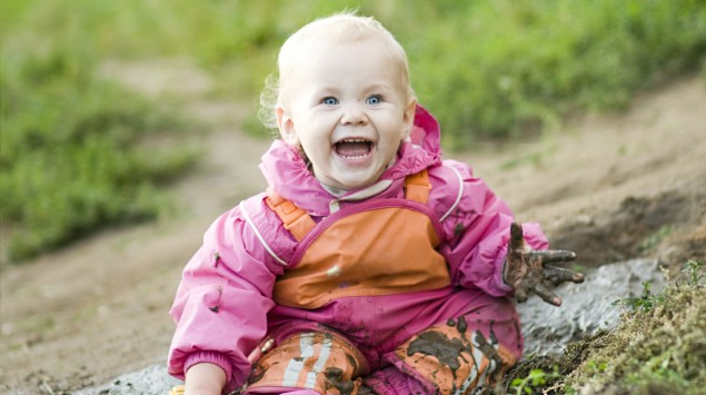 Ein Baby spielt im Matsch.